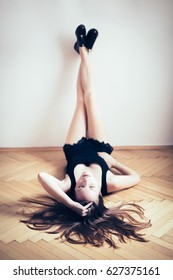 Young girl lying on floor (wooden parquet) with legs leaning against white wall. She is dressed in black shirt and skirt with lace, she has fashionable shoes and her long hair stretches across floor.