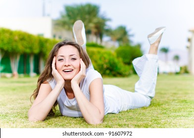 young girl lying on the grass in a white