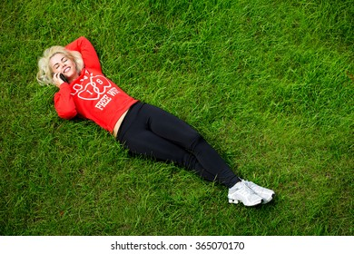 Young girl is lying on green grass talking on the phone