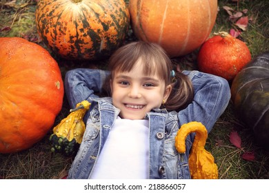 Young girl lying on the ground with pumpkins