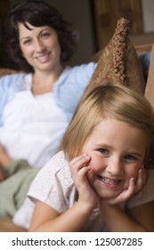 Young girl lying on sofa with her mother in the background