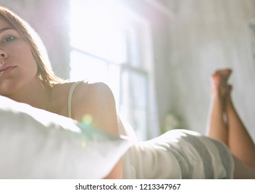 Young girl lying on a white bed on her stomach. Looking at the camera. The sun is shining outside.