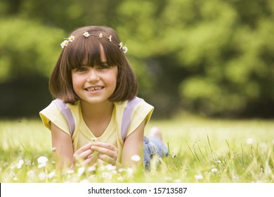 Young girl lying outdoors with flowers smiling