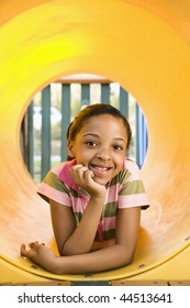 Young girl lying in yellow crawl tube at playground and smiling.