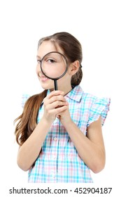 Young girl with magnifying glass on a white background
