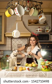young girl make canning with apple, there are a lot of dishes,  cat sits near