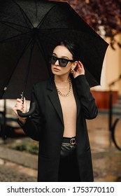 Young girl makes emotion.Dressed in a black shirt, black sweater, black hat, glasses and bright lips, fashion clothes.Wear vintage sunglasses, outfit and hat, leisure style, bright colors.Sensual woma