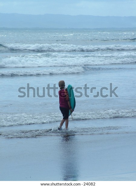 A young girl makes her first attempt at surfing.