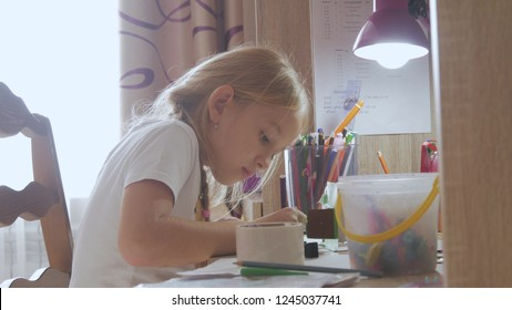 Young girl makes its homework at on the table under the light of a lamp. Creative hobby of little princess. lifestyle of talented people.