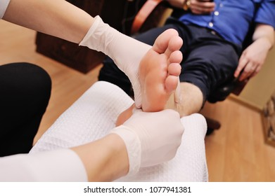 a young girl makes a man pedicure in the background of a beauty salon. Nail care