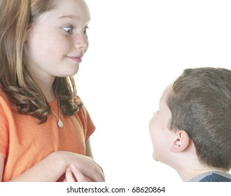 Young girl making boy laugh with silly face