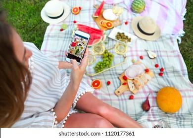 Young girl making food photo at summer picnic