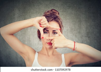 Young girl making frame with fingers and looking through limits at camera on gray background