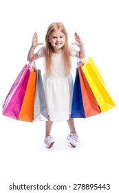 Young girl making a funny face with big shopping bags.