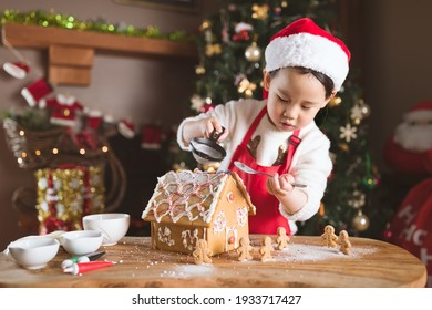 young girl making gingerbread house at home