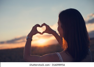 A young girl making heart symbol with her hands at sunset (lens focus on face)