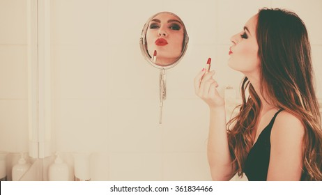 Young girl making makeup in bathroom. Woman take care about look. Looking into a mirror. Giving kiss