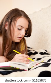 Young girl is making notes lying down on a bed