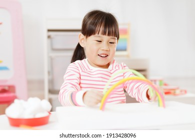 young girl making rainbow craft using pipe cleaner at home