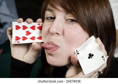 Young girl making silly face holding cards
