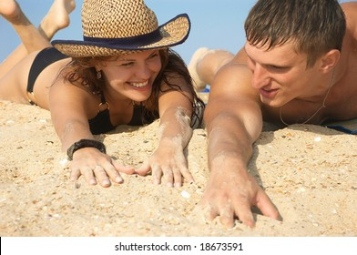 The young girl and man lay on sand