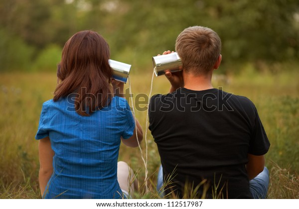 young girl and man playing with tin. outdoor shot