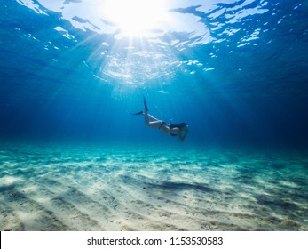 Young girl with mask and fins diving undewater on a clean blue sea.