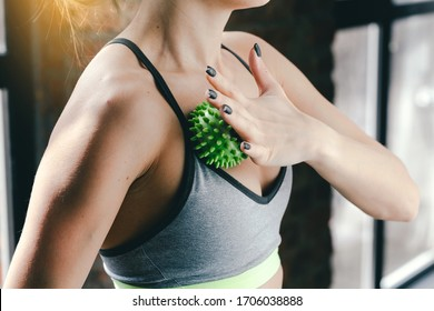 A young girl massages her chest with a green myofascial ball. Massage of the chest muscles
