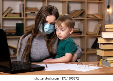 young girl in a medical mask sits with a baby in her arms. self-isolation of the house. large bookcase on the background. quarantined mom and son.