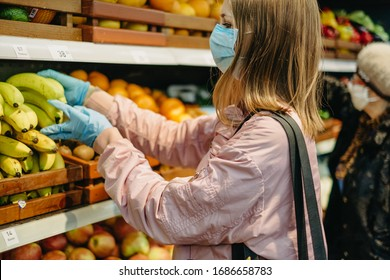 Young girl in medical masks makes purchases in a supermarket in search of food.