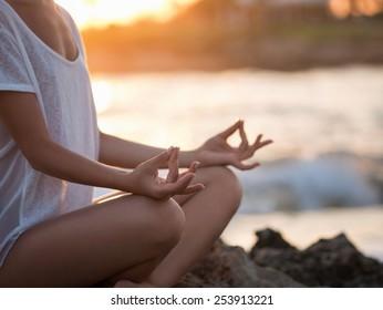 Young girl meditating at the sea