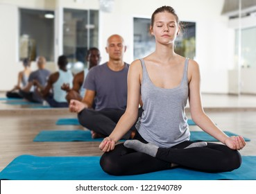 Young girl meditating in yoga position lotus during group training at gym