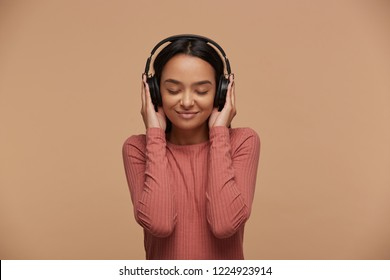 A young girl mixedrace listens to her favorite music in big black headphones, closing her eyes from pleasure, enjoyment, music lover, likes lyric songs about love, on beige background