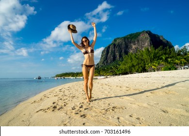Young girl model posing against a backdrop of picturesque palms, snow-white sand, ocean, boats and mountains. Mauritius Island, Indian Ocean