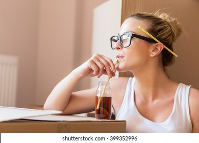 Young girl moving in a new apartment, sitting on the floor, drinking ice tea, surrounded with cardboard boxes