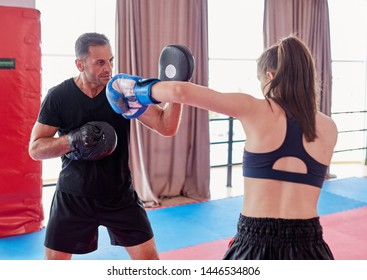 Young girl muay thai fighter and her coach hitting mitts in the ring