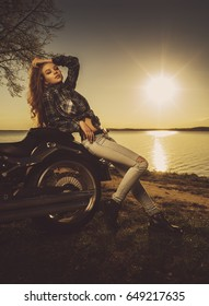 Young girl near the bike on the lake. Sunset. VIntage retro toned.