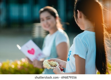 A young girl needs to give her mother with jasmine flower in Thai traditional Mother's Day festival on beautiful Sunday's morning in the central village park.