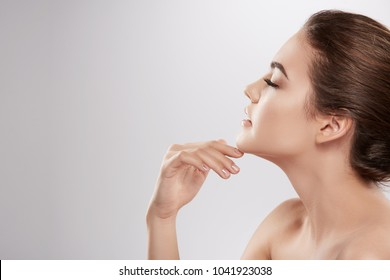 Young girl with nude make up and naked shoulders posing at grey background, beauty photo concept, skin care, hydrated skin, portrait, close up.