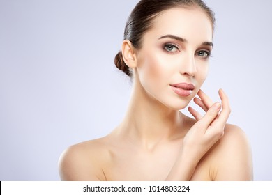 Young  girl with nude make up posing at grey studio background, beauty photo concept, looking at camera, perfect skin.