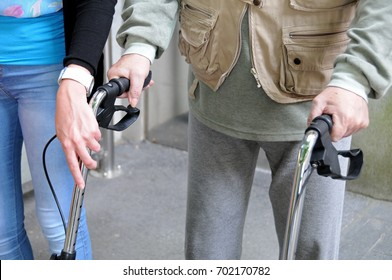 Young girl, an occupational therapist,  helps older man to walk with a rollator walker