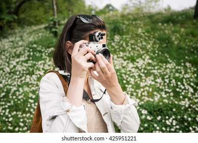 Young girl with an old camera taking pictures