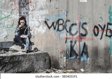 young girl in old dirty ragged clothes, no shoes sitting on a rock, and debris scattered around holding a cigarette and a match. Homeless girl. A homeless teenager.