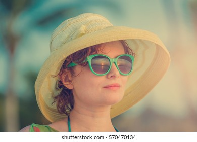 Young girl on the beach in green glasses during sunset