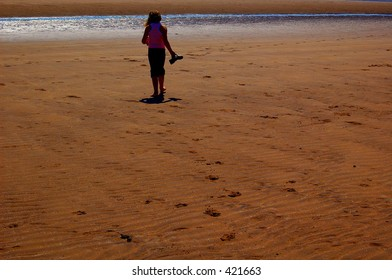 A young girl on the beach, heading toward the see, early evening, scotland 2005