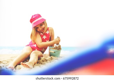 young girl on beach and toys on sand