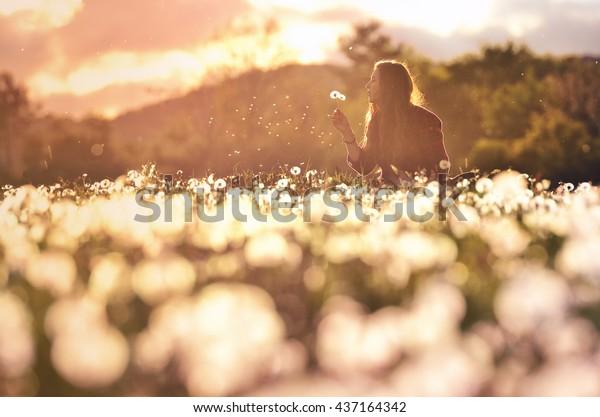 Junge Mädchen auf einer schönen, von Löwen befleckten Frühlingswiese.