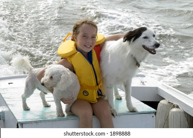 Young girl on boat with dogs