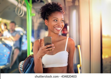 Young girl on the bus messaging with her smart phone