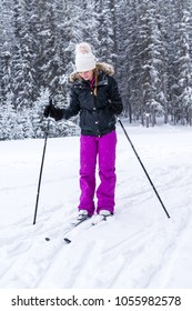 young girl on cross country skiis looking down at her skiis